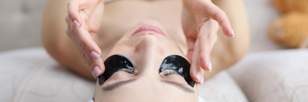 Женщина с полотенцем на голове, наклеивая черные пятна под глазами, концепция домашнего ухода за кожей