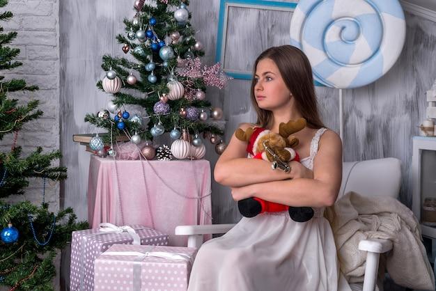 スタジオとクリスマスツリーのおもちゃを持つ女性。 2019年新年