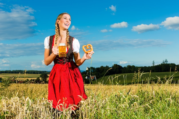 Woman with tracht, beer and pretzel in bavaria