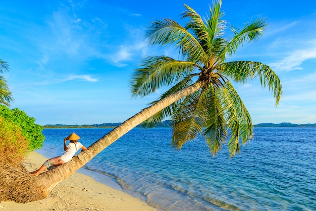 Woman with traditional asian hat relaxing on tropical beach sitting on coconut palm tree