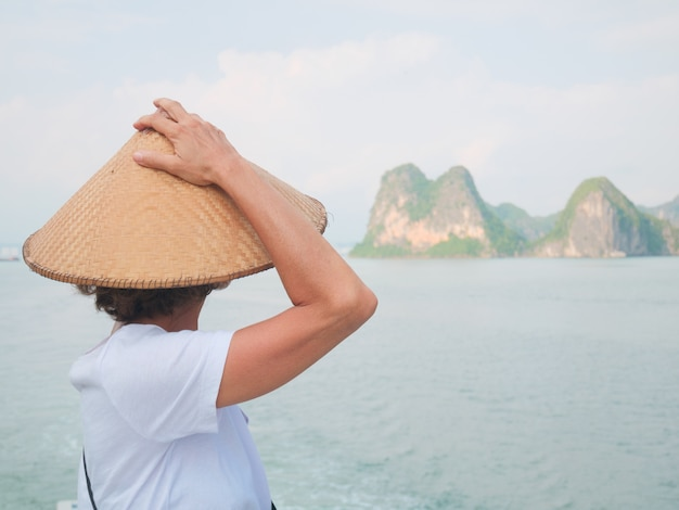 Woman with traditional looking at unique view of halong bay, vietnam.