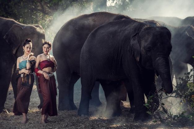 伝統的なタイのドレスの女性は象の村、スリン、タイで彼女の象を抱擁します。