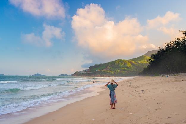 Женщина с традиционной вьетнамской шляпе, глядя на вид на тропическом пляже. quy hoa quy nhon вьетнамское туристическое направление, центральное побережье между данангом и нячангом