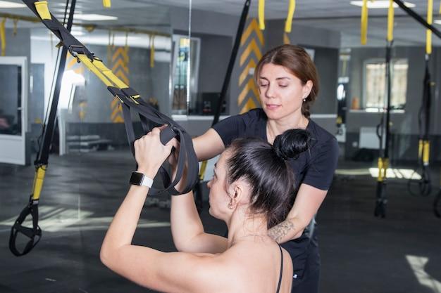 トレーナーを持つ女性がジムでスポーツに行く