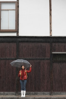Woman with transparent umbrella in rainy with wood wall. rainy season concept.