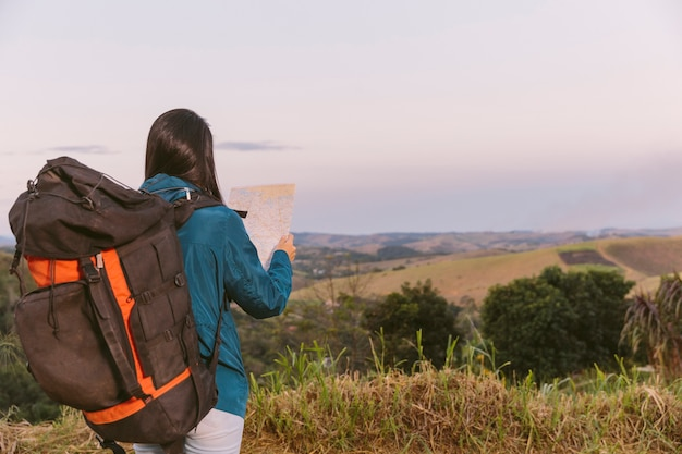 Woman with travel backpack looking in map