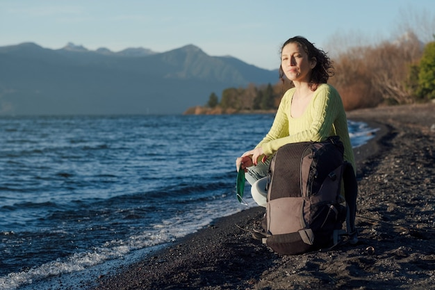 Woman with travel bag sitting on the shore of a lake