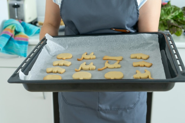 Woman with tray of halloween cookies for baking pastry shop copy space