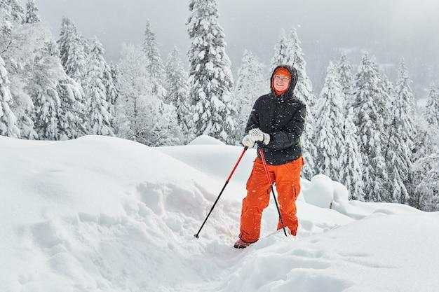 トレッキングポールを持つ女性は雪山に登って幸せです