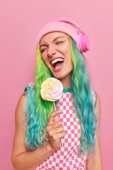 Женщина с модной цветной прической слушает музыку через беспроводные наушники, весело держит круглые карамельные конфеты на палочке, носит шляпу и клетчатое платье, изолированное на розовом