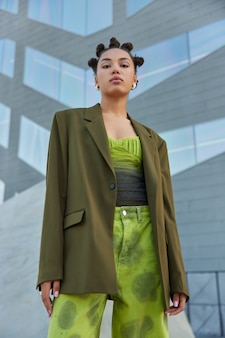 Donna con acconciatura alla moda trucco luminoso vestita con abiti alla moda posa contro il muro grigio fuori