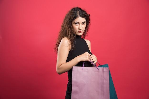 빨간색 바탕에 가방을 들고 까다로운 눈을 가진 여자