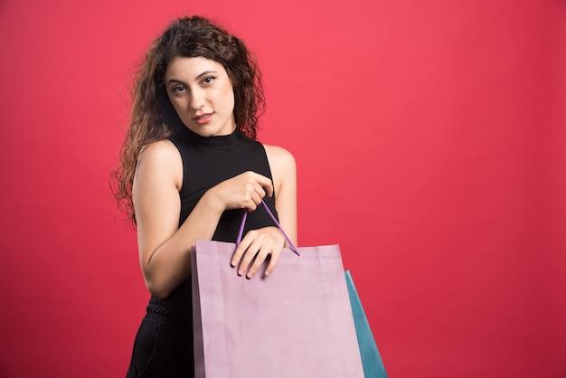 Женщина с хитрым взглядом держит сумки на красном фоне