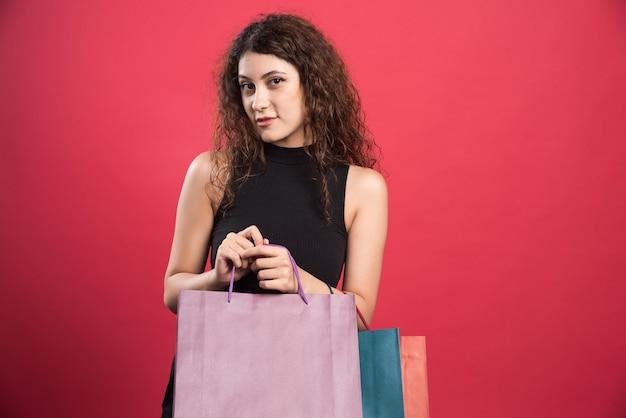 赤いバッグの多くを保持しているトリッキーな視線を持つ女性