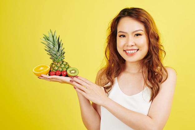 トロピカルフルーツを持つ女性