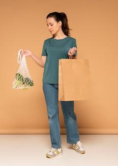 Donna con sacchetto di tartaruga e sacchetto di carta