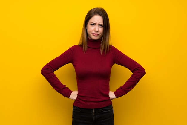 Woman with turtleneck over yellow wall angry