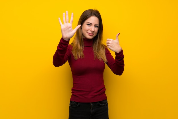 Woman with turtleneck over yellow wall counting six with fingers