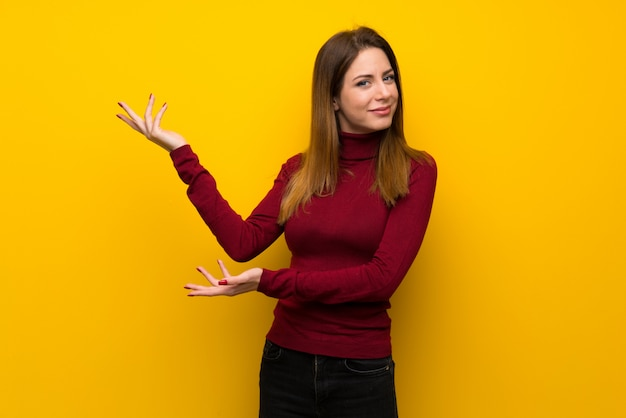 Woman with turtleneck over yellow wall extending hands to the side for inviting to come