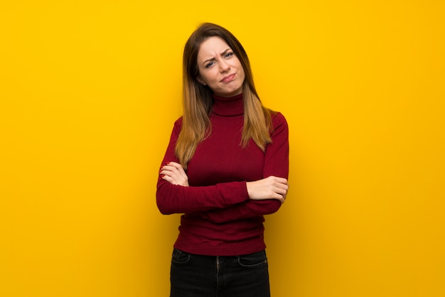 Woman with turtleneck over yellow wall feeling upset