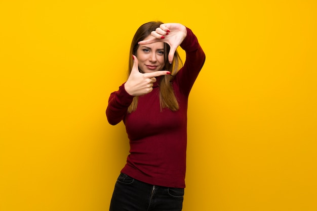 Woman with turtleneck over yellow wall focusing face. framing symbol