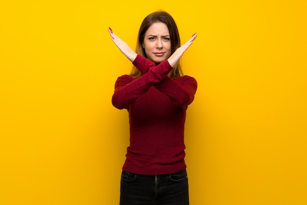 Woman with turtleneck over yellow wall making no gesture