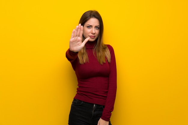 Woman with turtleneck over yellow wall making stop gesture denying a situation that thinks wrong