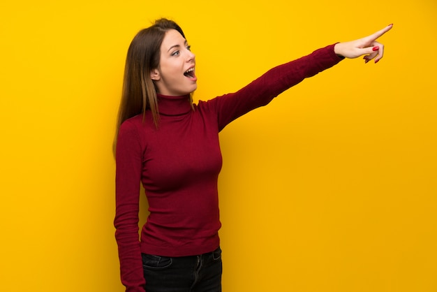 Woman with turtleneck over yellow wall pointing away