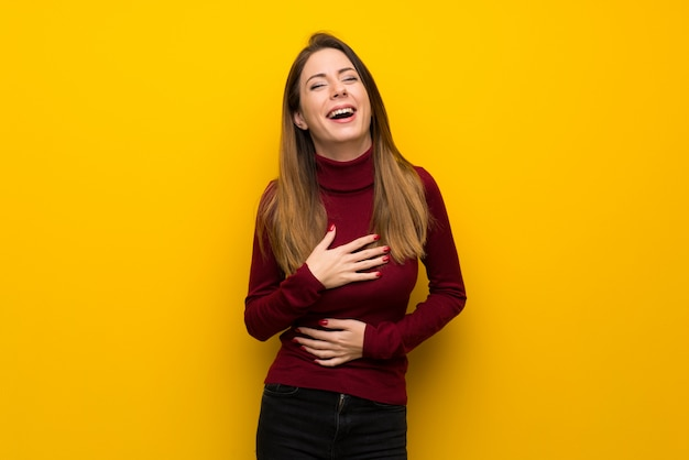 Woman with turtleneck over yellow wall smiling a lot