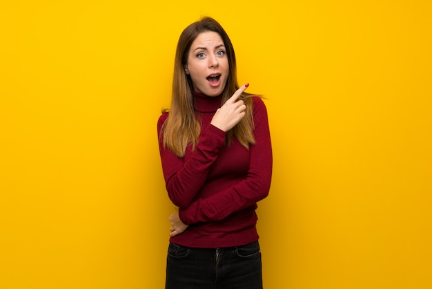 Woman with turtleneck over yellow wall surprised and pointing side