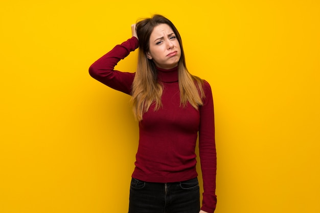 Woman with turtleneck over yellow wall with an expression of frustration and not understanding