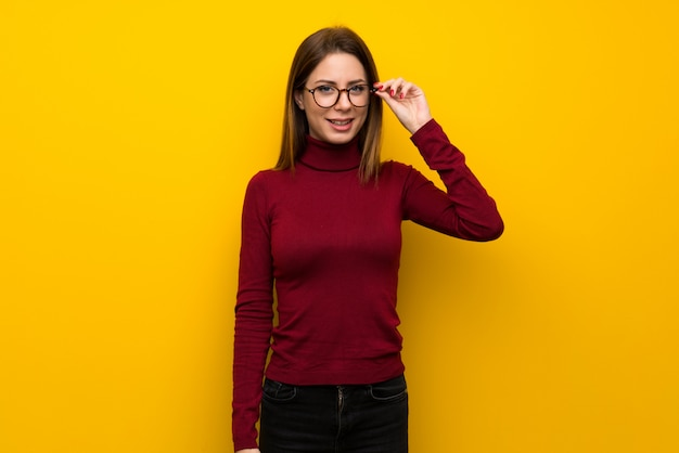 Woman with turtleneck over yellow wall with glasses and surprised