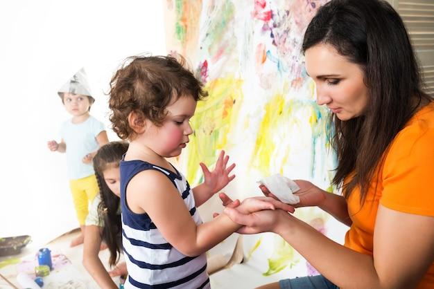 Женщина с двумя младенцами рисует красками и кистями, сидя за детским столом, красочная поверхность