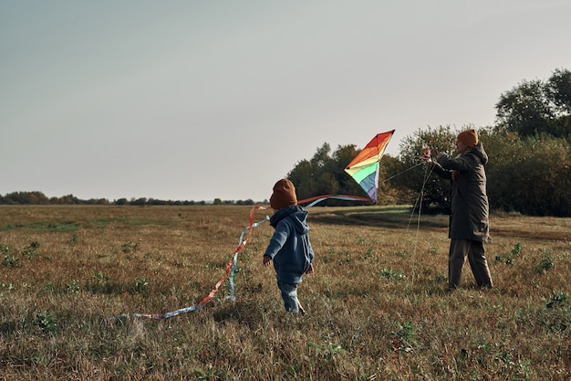 A woman with a two-year-old child is flying a kite. games with children, motherhood.