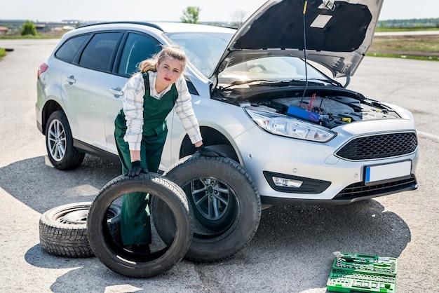 깨진 자동차 길가에 타이어를 가진 여자