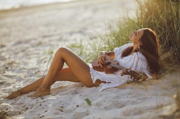 바다 근처 여름 해변 휴가 동안 우쿨렐레와 여자