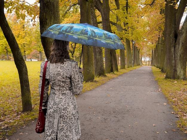 秋の公園で傘を持つ女性。