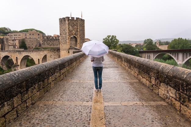 Женщина с зонтиком под дождем на мосту в средневековой деревне