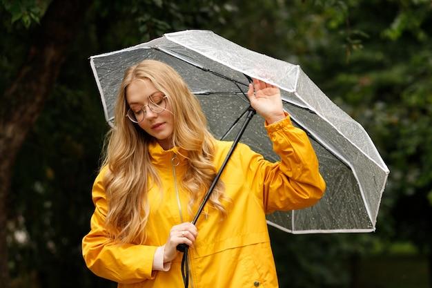 緑の背景に傘を持つ女性