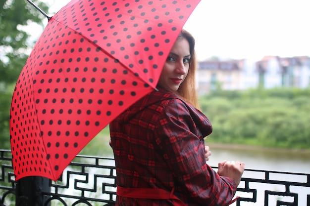 街路樹に赤い傘を持つ女性