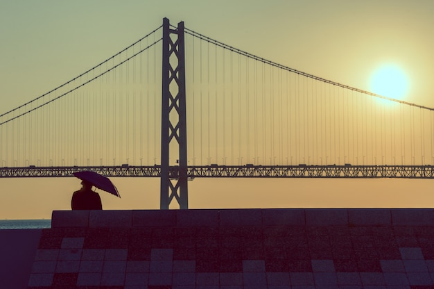 Woman with umbrella sitting at sunset with bridge in background, vintage pastel style