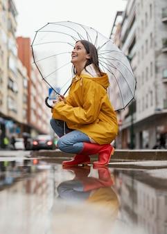 Женщина с зонтиком, стоя в дождь сбоку