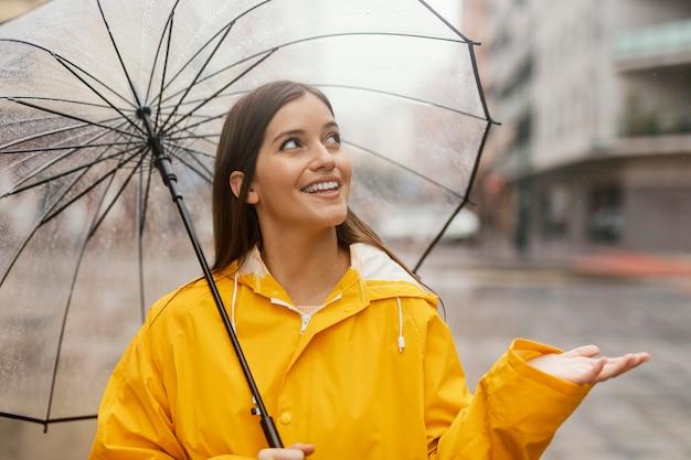 Женщина с зонтиком, стоя под дождем