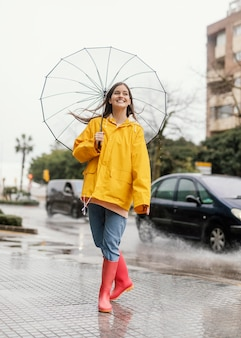 Woman with umbrella standing in the rain front view