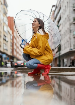 Woman with umbrella standing in the rain side view