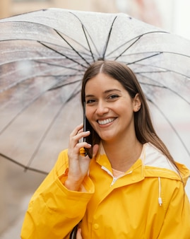 휴대 전화를 사용 하여 우산을 가진 여자