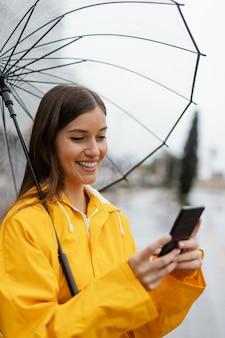 携帯電話を使用して傘を持つ女性