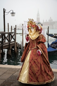 Woman with umbrella on the venetian lagoon background. venetian carnival outfit.