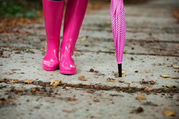 고무 장화를 입고 우산을 가진 여자
