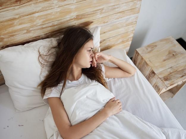 Женщина с несчастным выражением лица лежит в постели расстроенной Premium Фотографии